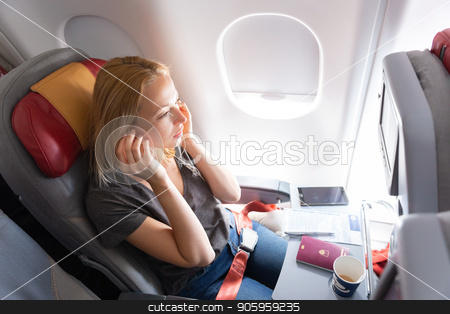 Woman flying on commercial passengers airplane, listening to music. stock photo, Woman flying on commercial passengers airplane, drinking coffee, listening to music. by kasto
