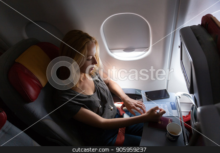 Casual woman flying on commercial passengers airplane, filling in immigration form. stock photo, Relaxed casual woman flying on commercial passengers airplane, filling in immigration form, drinking coffee, listening to music. by kasto