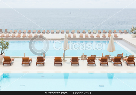 Luxury swimming pool with wooden deck chairs. stock photo, Luxury swimming pool with wooden sunbeds and umbrellas. by kasto