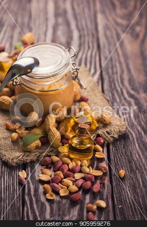 Natural peanut butter stock photo, Natural peanut butter with oil in a glass jar and peanuts by olinchuk