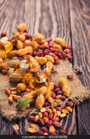 Natural peanut with oil in a glass stock photo, Natural peanuts with oil in a glass jar on the wooden background by olinchuk