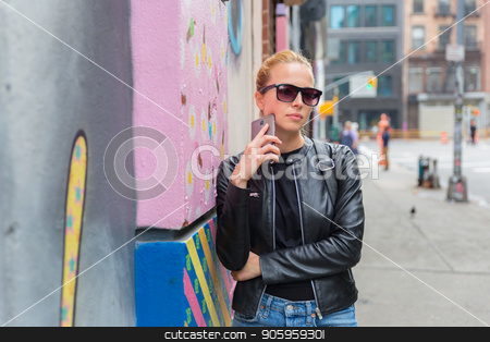Woman talking on smartphone leaning against colorful graffiti wall in New York city, USA. stock photo, Stylish woman talking on smartphone leaning against colorful graffiti wall in East Village, New York city, USA. by kasto