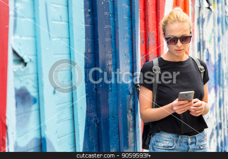 Woman using smartphone against colorful graffiti wall in New York city, USA. stock photo, Closeup of female hipster with smart phone. Woman using smartphone against colorful graffiti wall in East Village, New York city, USA. by kasto