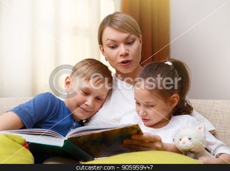 Beautiful mother is reading a book to her young children. Sister and brother is listening to a story. stock photo, Beautiful mother is reading a book to her young children. Sister and brother is listening to a story. Happy loving family. by Alfira Poyarkova