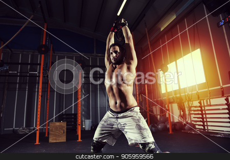 Athletic man works out at the gym with a kettlebel stock photo, Determined athletic man works out at the gym with a kettlebel by Federico Caputo