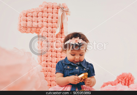 a little girl sitting on the floor among the flowers on a white background. Smiling child playing with a Golden toy stock photo, a little girl sitting on the floor among the flowers on a white background. Smiling child playing with a Golden toy by aaalll3110