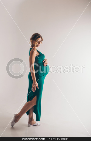 pregnant ballerina dancing on a white background. Future mother in a green dress posing stock photo, pregnant ballerina dancing on a white background. Future mother in a green dress posing by aaalll3110