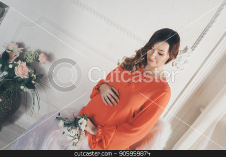 pregnant woman in red dress sitting on chair and stroking her belly stock photo, pregnant woman in red dress sitting on chair and stroking her belly by aaalll3110