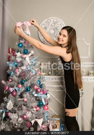 teenag girl decorates Christmas tree with Christmas toys stock photo, teenag girl decorates Christmas tree with Christmas toys. by Alexander