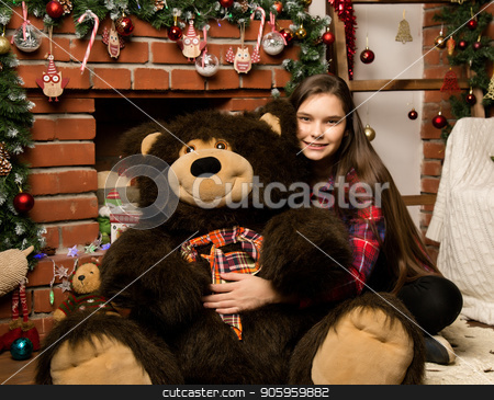 teenag girl is embraces a big big teddy bear on christmas near fireplace stock photo, teenag girl is embraces a big big teddy bear on christmas near fireplace. by Alexander