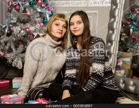 happy mother and teenag daughter near christmas tree at home laugh and hug stock photo, happy mother and teenag daughter near christmas tree at home laugh and hug. by Alexander