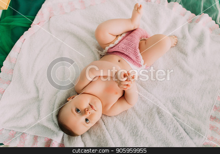 The above view of the lovely toddle lying on the white plaid. stock photo, The above view of the lovely toddle lying on the white plaid by Andrii Kobryn