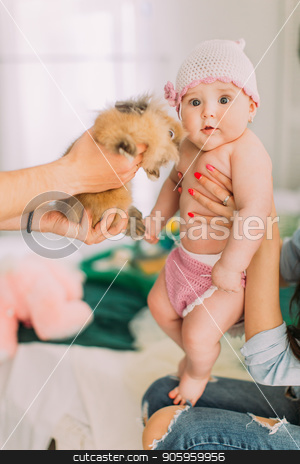 The vertical portrait of the lovely baby. The father is showing the rabbit. stock photo, The vertical portrait of the lovely baby. The father is showing the rabbit by Andrii Kobryn
