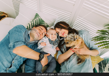 The close-up portrait of the happy family lying with the kid and rabbit on the bed. Above view. stock photo, The close-up portrait of the happy family lying with the kid and rabbit on the bed. Above view by Andrii Kobryn