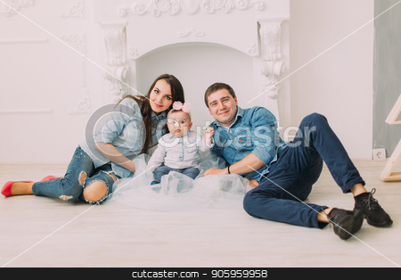 The horizontal portrait of the happy family with the baby sitting on the floor in the front of the white fireplace. stock photo, The horizontal portrait of the happy family with the baby sitting on the floor in the front of the white fireplace by Andrii Kobryn
