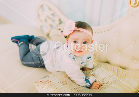 The front portrait of the little baby with the bow and flowers on the head lying on the white sofa. stock photo, The front portrait of the little baby with the bow and flowers on the head lying on the white sofa by Andrii Kobryn