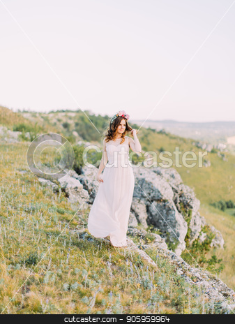 The full-length view of the bride touching her hair and looking aside at the backgroud of the mountains. stock photo, The full-length view of the bride touching her hair and looking aside at the backgroud of the mountains by Andrii Kobryn