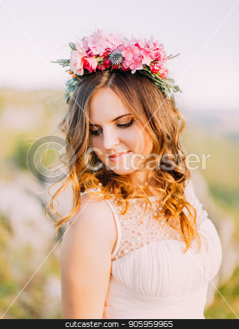 Close-up portrait of the cute bride with the wreath of flowers looking down. stock photo, Close-up portrait of the cute bride with the wreath of flowers looking down by Andrii Kobryn