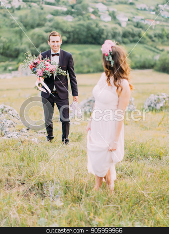 The groom with the wedding bouquet is walking to the bride in the meadow. stock photo, The groom with the wedding bouquet is walking to the bride in the meadow. by Andrii Kobryn