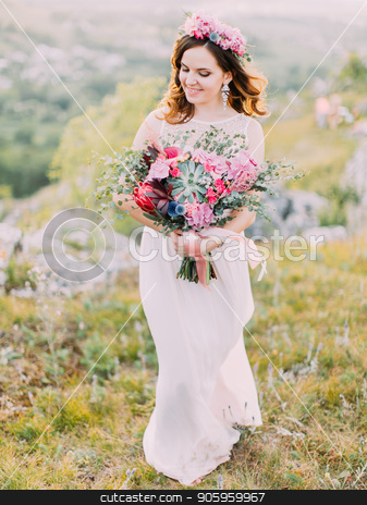 The up view of the smiling bride holding the huge wedding bouquet in the mountains. stock photo, The up view of the smiling bride holding the huge wedding bouquet in the mountains by Andrii Kobryn