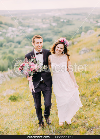 Happy newlywed couple is holding hands while walking in the mountains. stock photo, Happy newlywed couple is holding hands while walking in the mountains by Andrii Kobryn