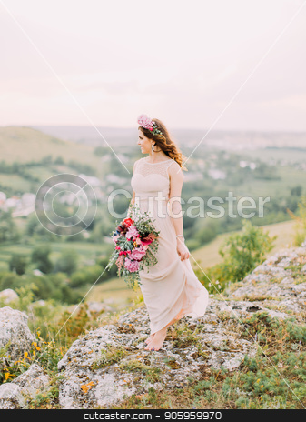 Full-length view of the beautiful bride with the wedding bouquet enjoying the landscape. stock photo, Full-length view of the beautiful bride with the wedding bouquet enjoying the landscape by Andrii Kobryn