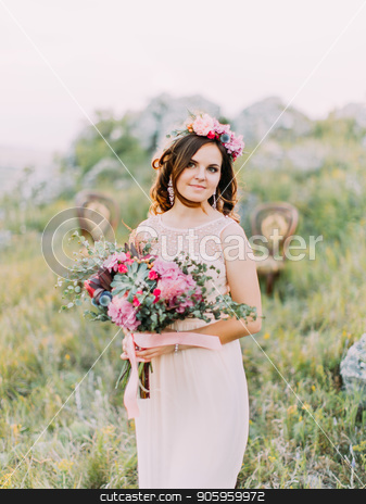 Half-length portrait of the smiling bride with the wedding bouquet in the mountains. stock photo, Half-length portrait of the smiling bride with the wedding bouquet in the mountains by Andrii Kobryn
