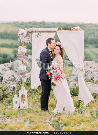 Sensitive outdoor portrait of the groom kissing the bride in the forehead near the wedding arch in the mountains. stock photo, Sensitive outdoor portrait of the groom kissing the bride in the forehead near the wedding arch in the mountains by Andrii Kobryn