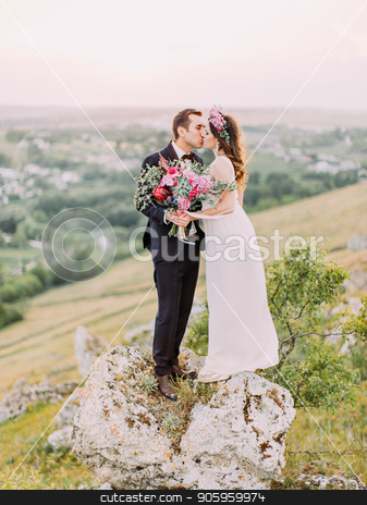 Lovely photo of the kissing newlyweds with the huge wedding bouquet while standing on the stone in the mountains. stock photo, Lovely photo of the kissing newlyweds with the huge wedding bouquet while standing on the stone in the mountains by Andrii Kobryn