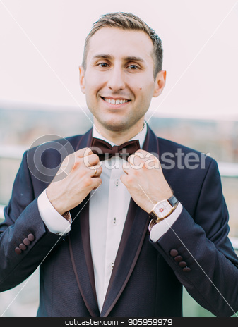 The close-up portrait of the smiling groom corresting the bow-tie. stock photo, The close-up portrait of the smiling groom corresting the bow-tie by Andrii Kobryn