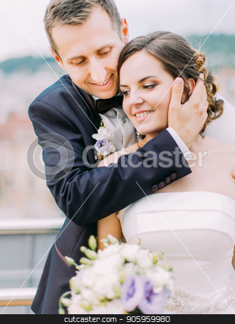 Romantic close-up portrait. Groom is hugging the bride back while stroking her cheek. stock photo, Romantic close-up portrait. Groom is hugging the bride back while stroking her cheek by Andrii Kobryn