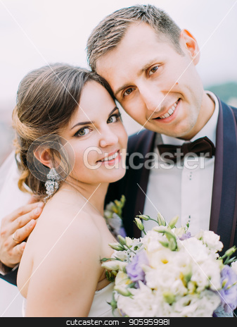 The smiling newlywed couple holding the wedding bouquet. Close-up portrait. stock photo, The smiling newlywed couple holding the wedding bouquet. Close-up portrait by Andrii Kobryn
