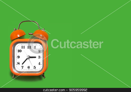 orange alarm clock on the green background stock photo, Vintage style orange metal alarm clock with bells standing on the green surface isolated. back to school concept. free space for text by Oleh