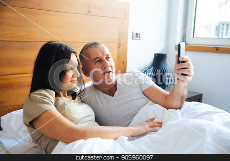 Couple Relaxing in the Bed stock photo, Attractive and Happy Mid Aged Couple Enjoying in the Bed in the Morning and Using a Smartphone and Taking Selfie Photo by Vera Arsic