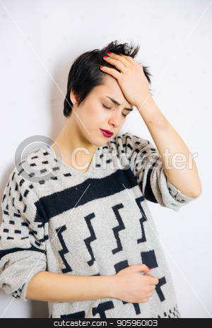 Anxious and depressed woman stock photo, Portrait of young upset and stressed woman standing near the wall with headache and lot of problems. by Vera Arsic