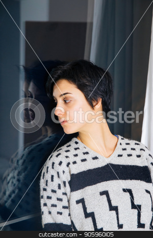 Beautiful girl standing at the window watching. stock photo, Lonely girl near window thinking about something. Melancholy reflection of the girl in the window. Sad and anxious girl standing near the window. by Vera Arsic