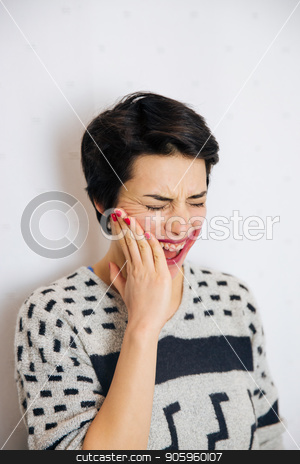 Anxious and depressed woman stock photo, Portrait of young upset and stressed woman standing near the wall with toothache and lot of problems. by Vera Arsic