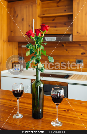 Ready For Anniversary stock photo, Three Red Roses In Bottle And Two Glasses Of Red Wine On Wooden Table by Vera Arsic