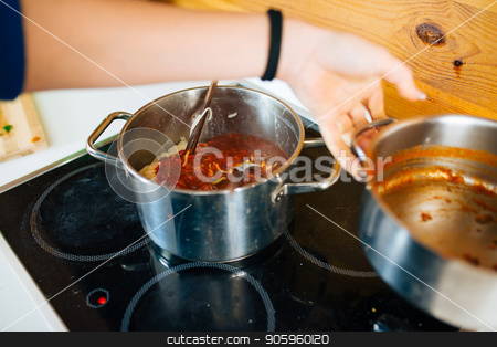 Delicious Spaghetti Preparation stock photo, View of Woman Preparing a Tomato Sauce For Pasta in The Kitchen by Vera Arsic