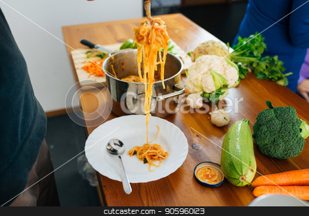 Preparing an Italian Food stock photo, Close View of Woman Preparing a Delicious Spaghetti in The Kitchen. Healthy Food Concept. by Vera Arsic