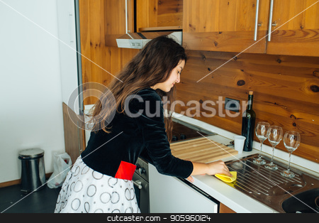 Daughter Polishing The Kitchen stock photo, Cute Little Girl Is Cleaning The Kitchen With Yellow Rag by Vera Arsic