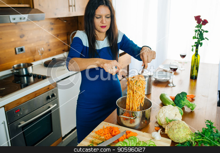 Happy Joyful Mother Cooking A Pasta. Healthy Food Concept. stock photo, Attractive Woman In Blue Dress Is Preparing Delicious Spaghetti Food In The Kitchen by Vera Arsic