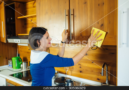 Woman in the Kitchen stock photo, Attractive Long Haired Woman In Blue Dress Is Polishing The Kitchen With Yellow Rag by Vera Arsic