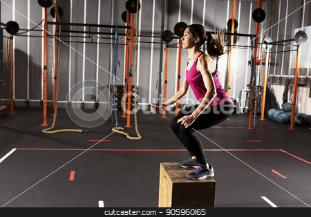 Athletic girl does box jump exercises at the gym stock photo, Determined athletic girl does box jump exercises at the gym by Federico Caputo