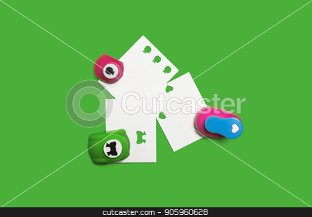 three hole punchers with papers stock photo, three small colored plastic hole punchers with sheets of paper standing on the green background. concept of office chancery. free space for text by Oleh