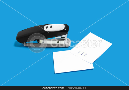 black stapler with sheets of paper stock photo, metal black stapler with sheets of paper memorandums lying on a blue background . concept of office chancery. free space for text by Oleh