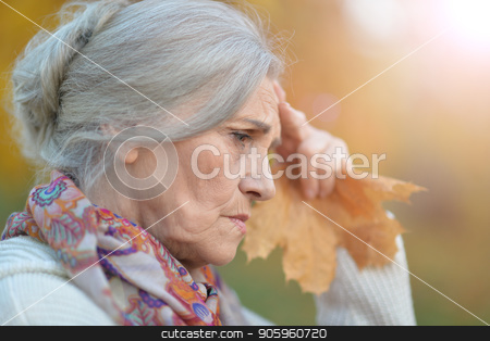sad senior woman in autumn park stock photo, Portrait of sad senior woman in autumn park by Ruslan Huzau