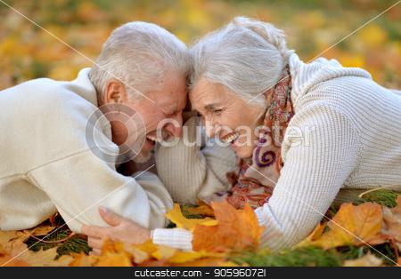 happy senior couple posing in autumn park stock photo, Portrait of happy senior couple posing in autumn park by Ruslan Huzau