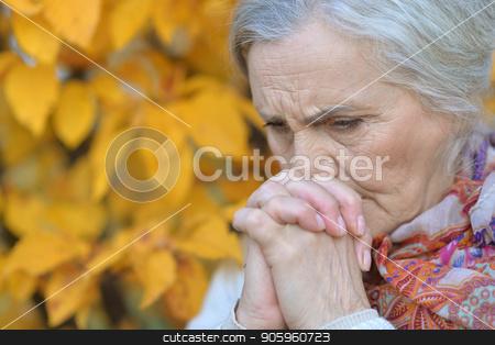 sad senior woman in autumn park stock photo, Portrait of sad senior woman in autumn park by Ruslan Huzau