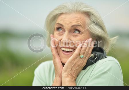 smiling  elderly woman stock photo, Portrait of happy smiling elderly woman posing outdoors by Ruslan Huzau